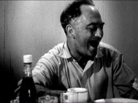 1941 medium shot man at diner counter with missing teeth laughing - kopf schütteln stock-videos und b-roll-filmmaterial