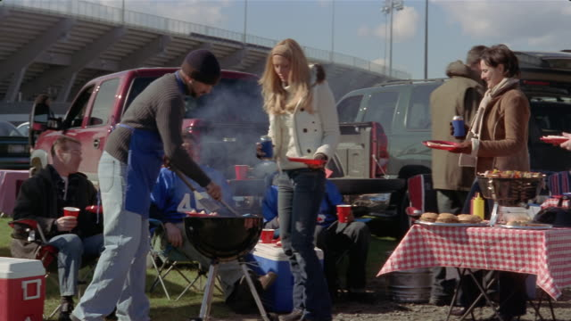medium shot man at grill serving burgers at tailgate party/ connecticut - cool box stock videos & royalty-free footage