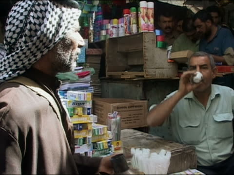 2003 medium shot man at market stall drinking tea / vendor refilling his cup from brass pot / baghdad iraq - beccuccio video stock e b–roll