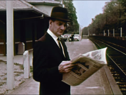 1964 medium shot man at railway station reading newspaper and waiting / long island, new york / audio - long island railroad stock videos & royalty-free footage