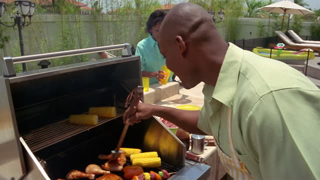 vídeos y material grabado en eventos de stock de medium shot man barbecuing at grill and woman pouring lemonade in yard / boy being served barbecue + lemonade - cocido a la parrilla