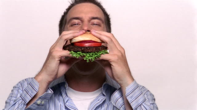 medium shot man biting into hamburger - hamburger stock videos & royalty-free footage