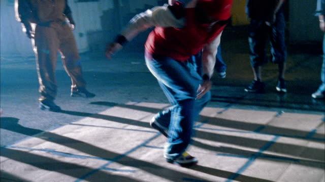 medium shot man breakdancing in warehouse as people watch - baggy jeans stock videos & royalty-free footage