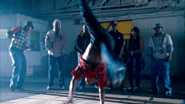vídeos de stock e filmes b-roll de medium shot man breakdancing in warehouse as people watch - funky