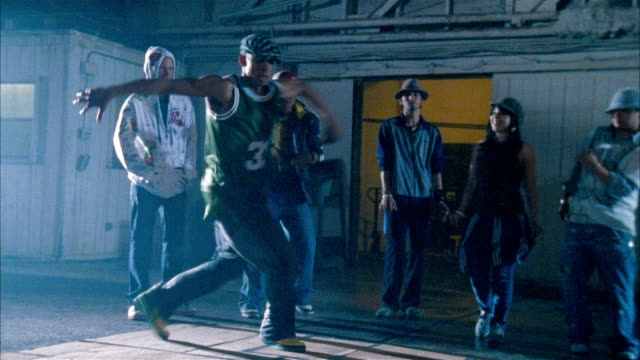 Medium shot man breakdancing in warehouse as people watch