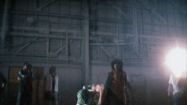 vídeos de stock e filmes b-roll de medium shot man breakdancing in warehouse as people watch - povo jamaicano
