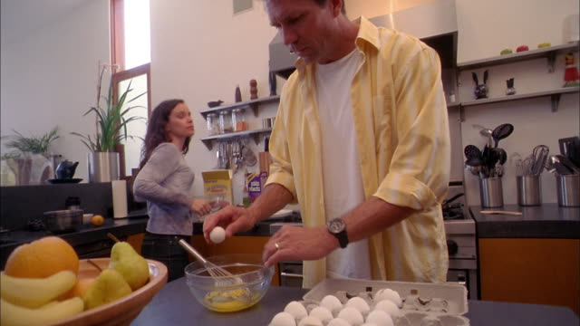 medium shot man breaking eggs into bowl and scrambling them w/whisk / woman + boy in background - breakfast stock videos and b-roll footage