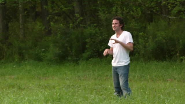 Medium shot man catching and throwing frisbee