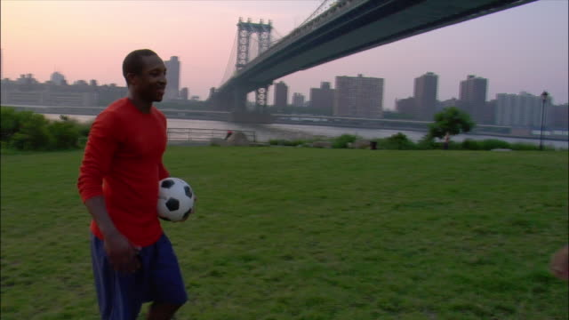 medium shot man catching soccer ball / two men hugging in park with manhattan bridge in background / sunset / dumbo, brooklyn, new york - catching stock videos & royalty-free footage