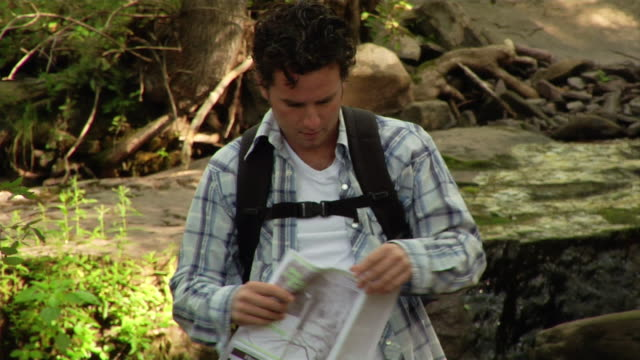 medium shot man checking map during hike - folded stock videos and b-roll footage