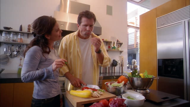 Medium shot man chopping vegetables on kitchen cutting board / woman talking to him