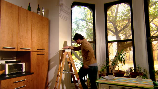 medium shot man climbing ladder in kitchen and measuring moulding by window/ brooklyn, new york - pot plant stock videos and b-roll footage