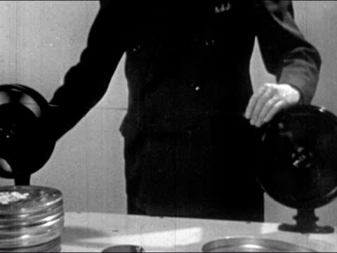 vidéos et rushes de 1943 medium shot man cranking film reels, transferring film from one reel to other - boîte de film