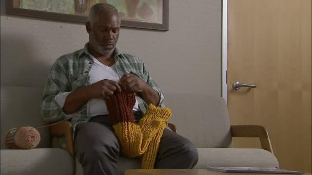 Medium shot man crocheting scarf in doctor's office waiting room