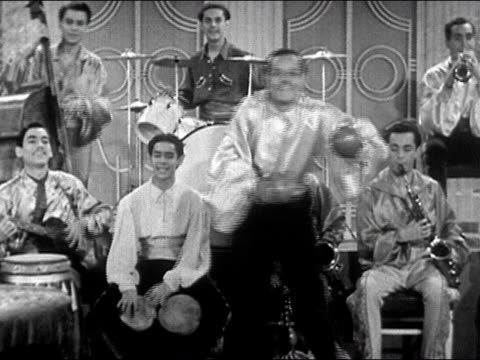 1941 medium shot man dancing with maracas as latin big band plays in background/ audio - halbnahe einstellung stock-videos und b-roll-filmmaterial