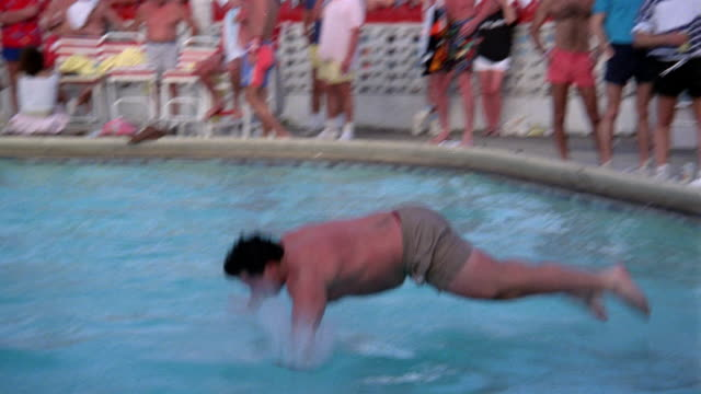 vídeos de stock e filmes b-roll de medium shot man diving into pool during belly flop contest / miami - esquisito