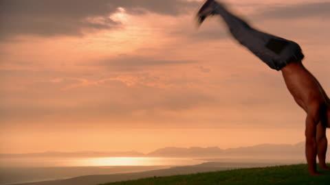 medium shot man doing backflips with water in background / somerset west, south africa - torso bildbanksvideor och videomaterial från bakom kulisserna
