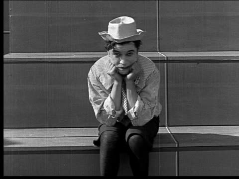 1918 b/w medium shot man dressed as child sitting on steps alone, looking frustrated - uncomfortable stock videos & royalty-free footage