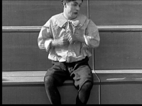 1918 b/w medium shot man dressed as child sitting on steps looking frustrated/ pulling out pocket knife and attempting to cut foot - pocket stock videos & royalty-free footage
