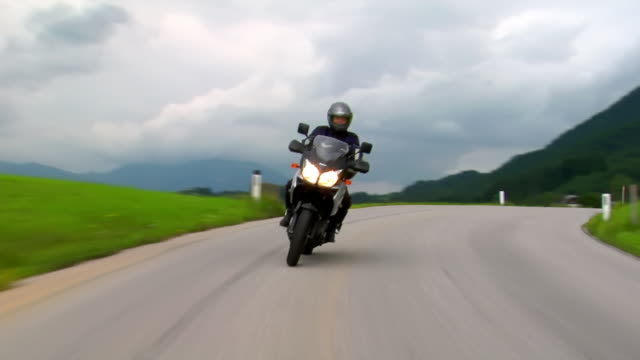 medium shot man driving motorcycle along country road through hillside/ austria - motorbike stock videos & royalty-free footage
