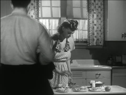 vídeos de stock e filmes b-roll de 1945 medium shot man entering kitchen and kissing wife / wife looking concerned after he leaves - cozinha doméstica