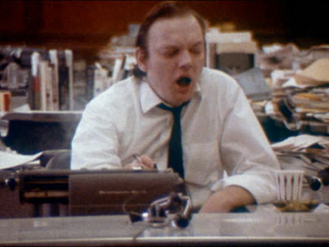 1970 medium shot man exhaling cigarette smoke at desk / yawning for long time