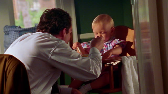 medium shot man feeding baby, then looking over his shoulder - genderblend video stock e b–roll