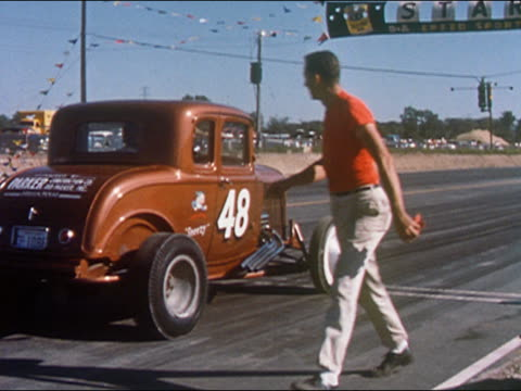 vídeos de stock e filmes b-roll de 1959 medium shot man finished checking tire of bronze car  / race car taking off and speeding down track - 1950 1959