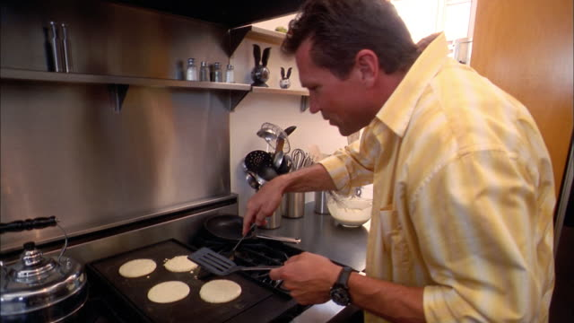 medium shot man flipping pancakes on stove w/spatula - etwas herstellen stock-videos und b-roll-filmmaterial