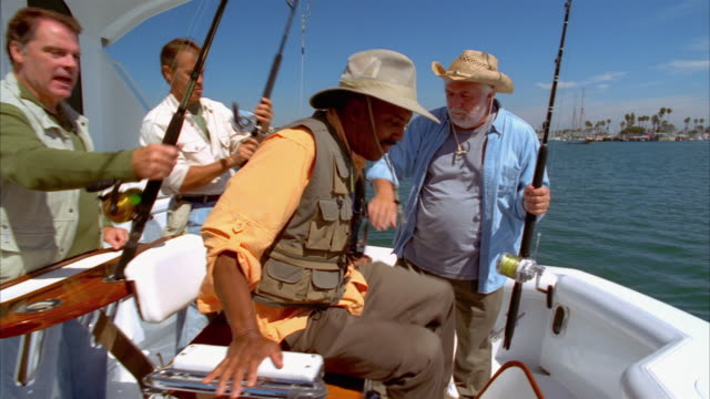 Medium shot man getting into fighting chair as captain shows him how to hold fishing rod/ Long Beach, California
