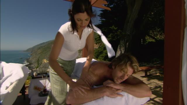 medium shot man getting massage with ocean in background/ monterey county, california - massagetisch stock-videos und b-roll-filmmaterial