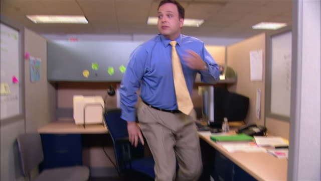Medium shot man getting up from desk and going to co-worker's cubicle to look for him / man hiding under desk getting up and sneaking away