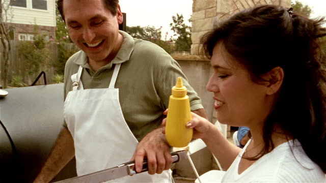 Medium shot man giving woman hot dog / tracking shot woman putting mustard on hot dog and walking to table