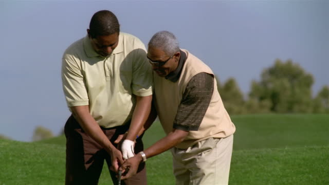 medium shot man helping friend with golf grip - golf glove stock videos and b-roll footage