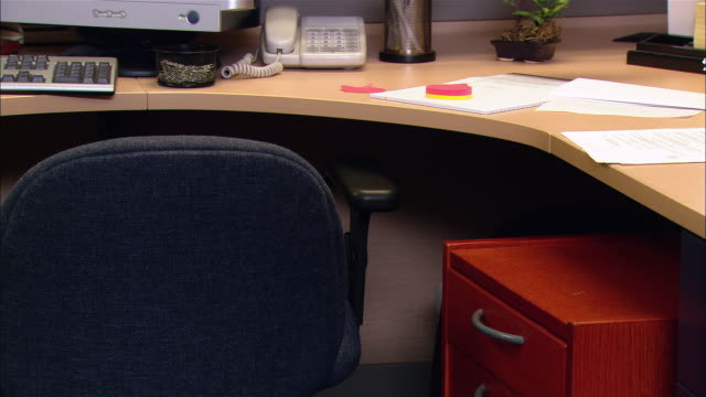 Medium shot man hiding under desk in cubicle / poking head out and looking around / going back under desk