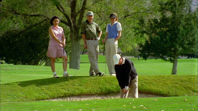 vidéos et rushes de medium shot man hitting golf ball in sand pit with woman and another couple watching in background - casquette de baseball