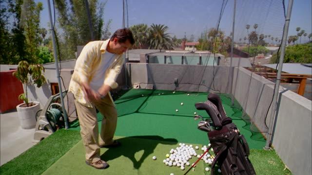 vídeos de stock, filmes e b-roll de medium shot man hitting golf balls into net on rooftop practice green - bolsa de golfe