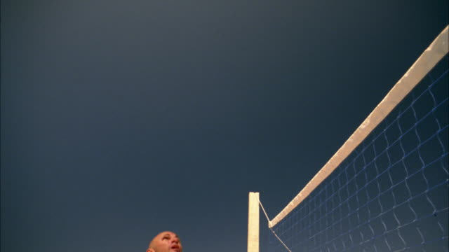 medium shot man hitting soccer ball off chest and over net in beach volleyball game - volleyball net stock videos & royalty-free footage