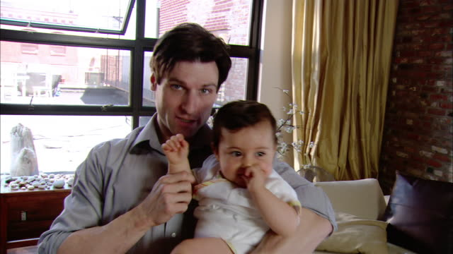 medium shot man holding baby on his lap and making her wave at the camera - genderblend stock videos & royalty-free footage