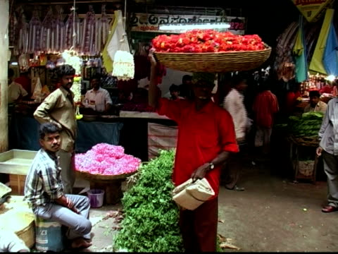 Medium shot man holding basket of flowers on his head at market