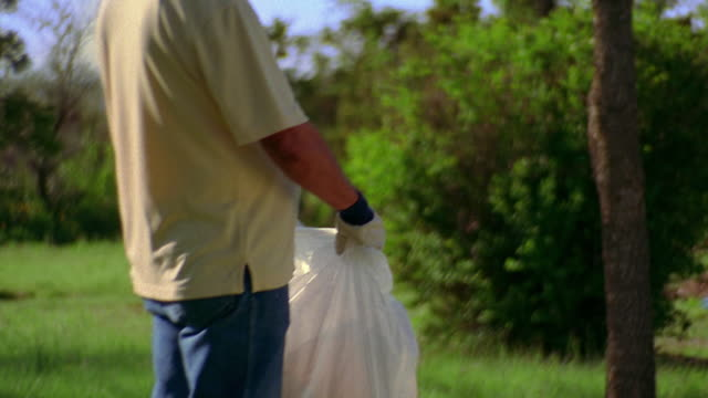 medium shot man holding trash bag with girl putting bottle in it outdoors / new mexico - granddaughter stock videos & royalty-free footage