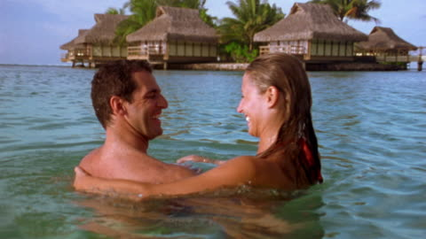 medium shot man holding woman and spinning her in water w/huts in background / tahiti - 30 39 years stock videos & royalty-free footage