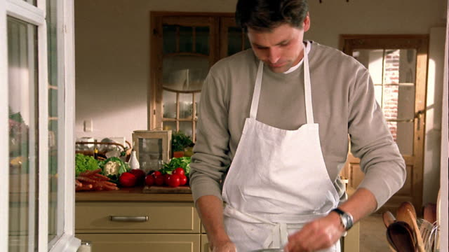 Medium shot man in apron stirring and tasting pasta in pot + wiping hands on apron in kitchen / Belgium