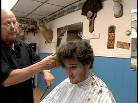 medium shot man in barber shop making faces as barber cuts his long hair - shaving brush stock videos & royalty-free footage