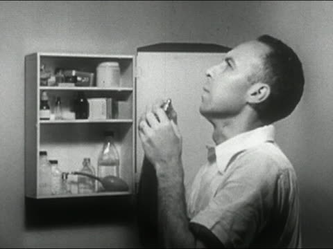 1955 Medium shot man in bathroom in front of open medicine cabin with head back repeatedly using nasal spray / AUDIO
