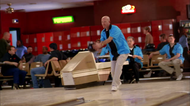 Medium shot man in blue team jersey bowling and cheering