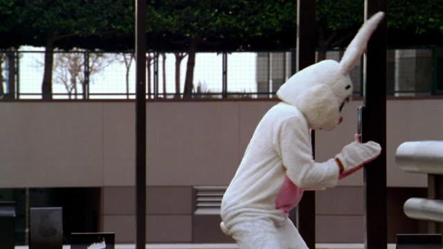 medium shot man in bunny costume pushing and kicking pedestrian signal changer before crossing street + falling - kelly mason videos stock videos & royalty-free footage
