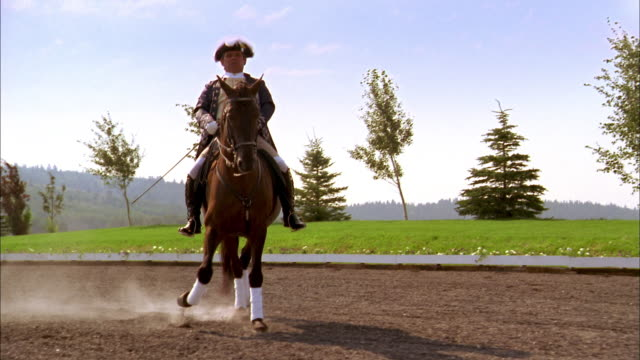 Medium shot man in colonial costume on horse side-stepping on dirt track/close up on hooves