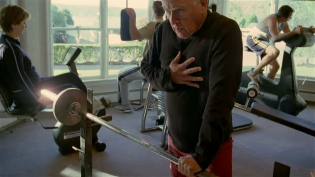 vídeos de stock, filmes e b-roll de medium shot man in gym holding onto barbell and grabbing chest as if having heart attack/ solebury, pennsylvania - heart attack