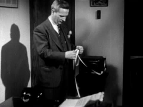 1946 medium shot man in office reading ticker tape coming from machine - telegraf stock-videos und b-roll-filmmaterial